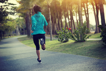 sporty fitness woman running at tropical park