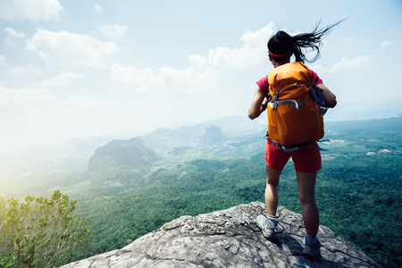 Young woman with backpacker hiking at seaside mountain cliff edge