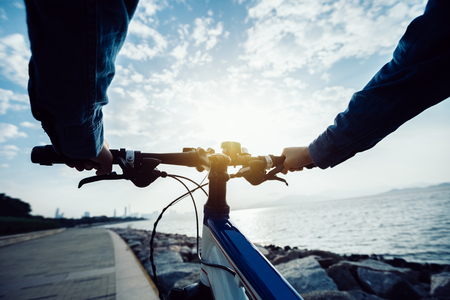 cyclist riding bike in the sunrise coast path