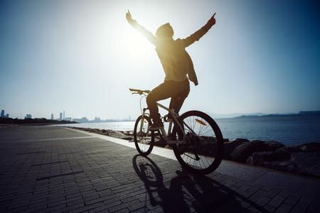 silhouette cyclist riding bike in the sunrise coast road Stock Photo