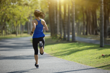 sporty young fitness woman running at tropical park Stock Photo