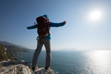 woman backpacker enjoying the view on morning mountain valley Stock Photo
