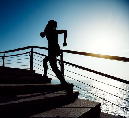 Sporty fitness female runner running up on seaside stairs