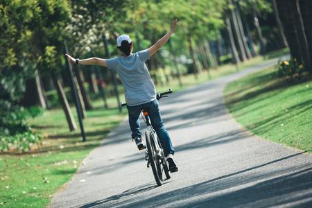 happy woman cyclist riding bike on tropical park