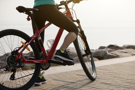 Woman cyclist riding mountain bike on seaside Archivio Fotografico