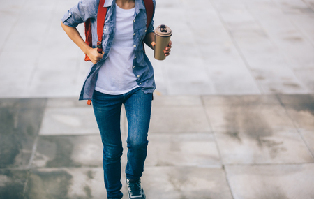 Woman walking with coffee themo cup in hand Archivio Fotografico