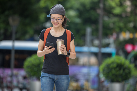 Walking with coffee themo cup in hand and use cellphone on city street
