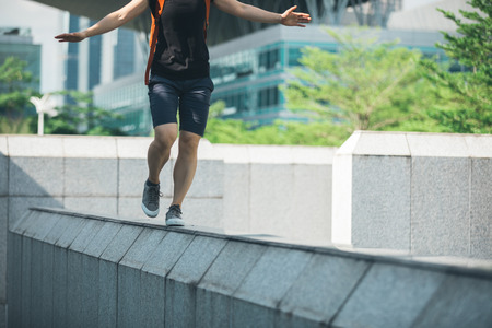 Woman walking on the edge of a urban building wall at city Stock Photo