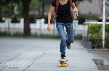 woman skateboarding with coffee cup in hand on city street