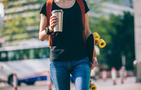 Woman walking with skateboard in hand on city street