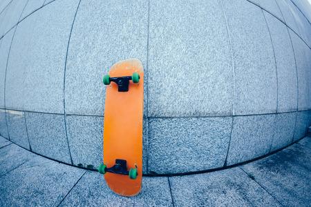 One skateboard against grey concrete wall