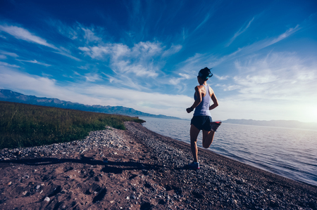 Young fitness sporty woman running on rocky seaside Stock Photo