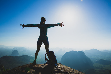 Successful cheering young woman hiker outstretched arms on sunrise mountain peak cliff edge 免版税图像