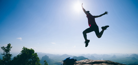 Young woman backpacker jumping