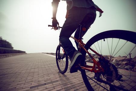 cyclist riding mountain bike in the sunrise coast Stock Photo