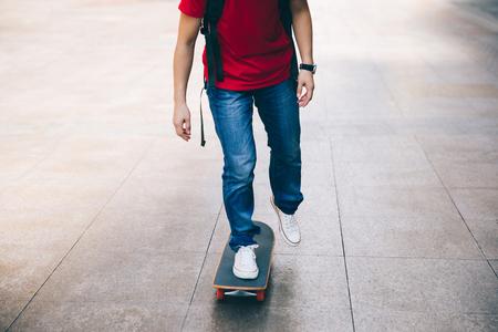 Piernas de skater montando patineta en las calles de la ciudad