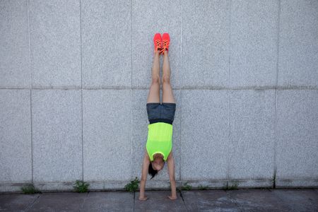 Sportswoman doing a handstand against a marble wall Stock Photo