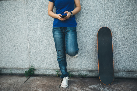 one skateboarder use mobile phone on city