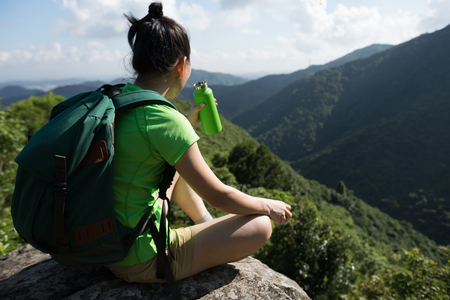 Successful woman hiker drinking water on hiking travel