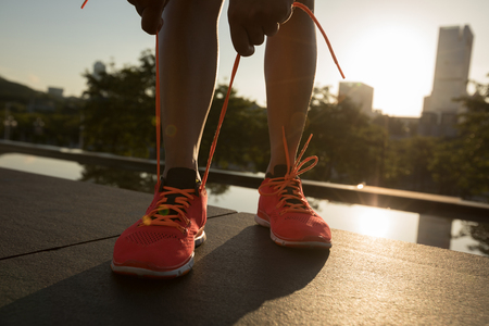 Healthy lifestyle woman runner tying shoelace before running