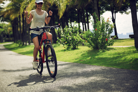 Happy woman ride bike in sunny tropical park