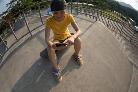 skateboarder sit on skateboard use mobile phone 版權商用圖片