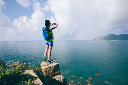 Woman Hiking In Seaside Taking A Selfie with mobile phone