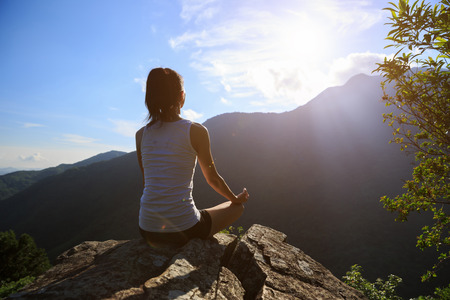 Yoga woman meditating on mountain peak cliff edge in the sunrise