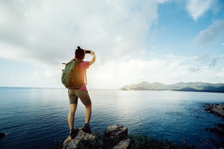 Hiking woman standing by the seaside taking  selfie with mobile phone