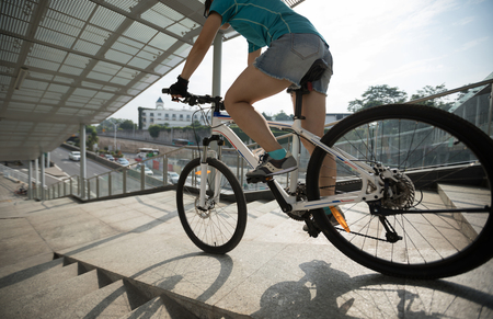 Woman freerider riding down ramp of overpass in city Stock Photo
