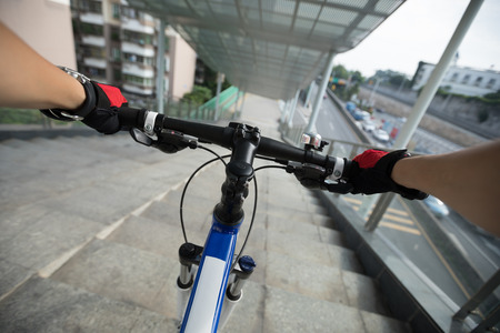 Riding bike down stairs of overpass in city 免版税图像
