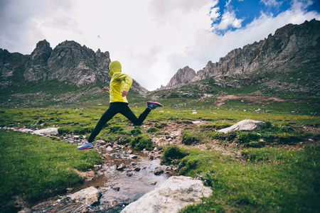 Woman trail runner jumping over small river on mountains