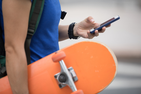 Woman with skateboard in hand using smartphone in modern city