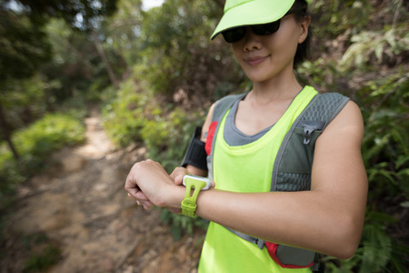 Asian woman set the sports watch before trail running on mountain