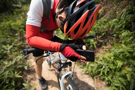 Tired woman cyclist have a rest with mobie phone in hands