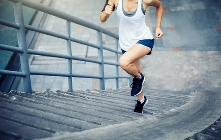 Young woman runner sportswoman running up city stairs 스톡 콘텐츠