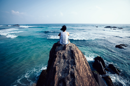 Young woman sit on seaside rock cliff edge looking at the distance