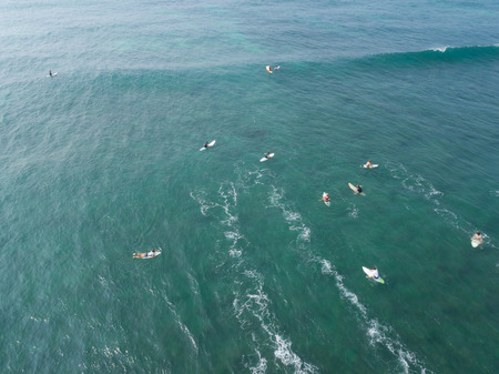 Top view from drone of many surfers waiting  to catch next wave during surf  in the indian ocean Stock Photo