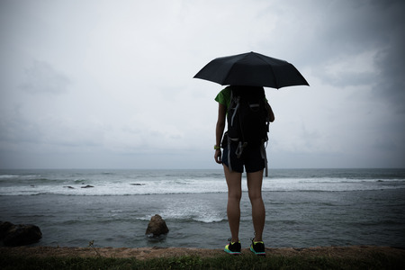 Woman with umbrella stand in the strom infront of sea
