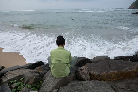 Sad asian woman sit on beach. Back view