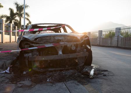 closeup of a burned out car on roadside
