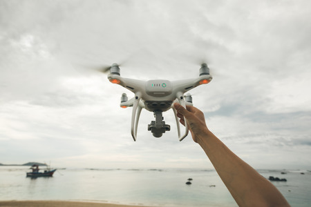 Hand reaching out for a flying drone which taking photo over sea