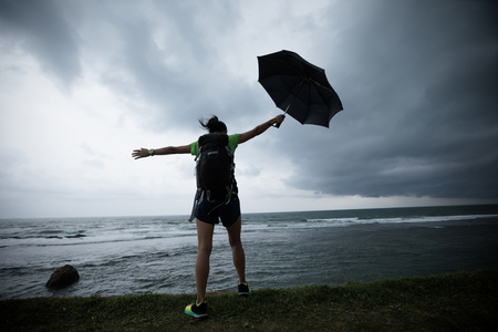 woman with umbrealla stand in the storm at seaside Stok Fotoğraf