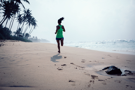 Fitness healthy lifestyle young woman running on tropical beach during sunrise in the morning