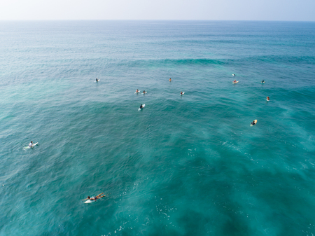 Aerial view from drone of surfers paddling for catching waves during surfing in the indian ocean Stock Photo