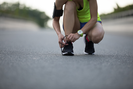 Sportswoman tying shoelace before running on city street