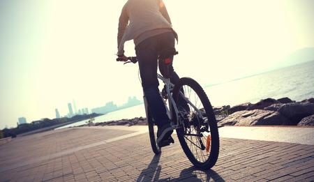 Silhouette cyclist riding bike in the sunrise coast road Archivio Fotografico