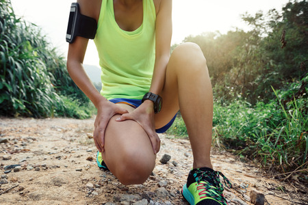Asian woman runner hold her sports injured leg on mountain trail