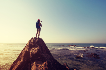 woman photographer taking photo sit on seaside rock cliff edge Reklamní fotografie
