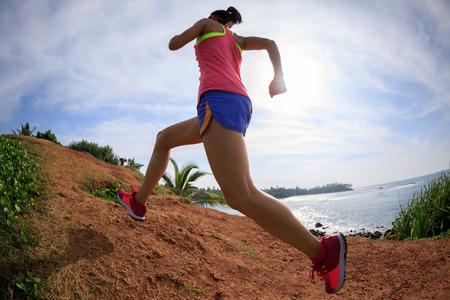 Woman trail runner running on seaside hills